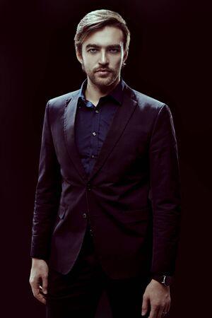 Businessman portrait. Handsome man in elegant formal suit on a black background. Business style. Studio shot.