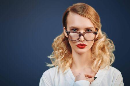 Studio portrait of a fashionable blonde woman in elegant glasses. Optics, eyewear. Copy space.