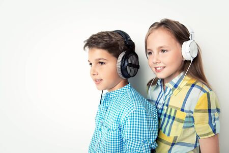 A portrait of two cheerful young kids listening to music in headphones over the white background. Summer casual kids fashion. 版權商用圖片