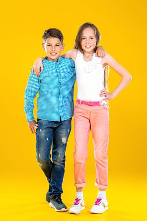 A portrait of two cheerful young kids over the yellow background. Summer casual kids fashion. 版權商用圖片