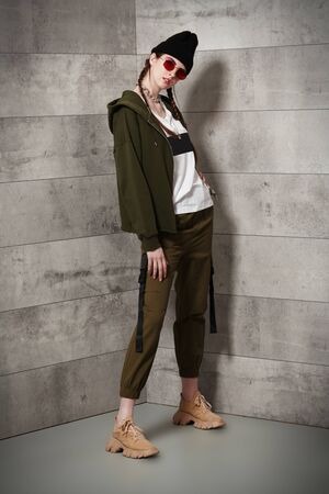 Youth fashion. Trendy young girl with bright make-up wears khaki clothing, black hat and red sunglasses on a loft background. Urban style.