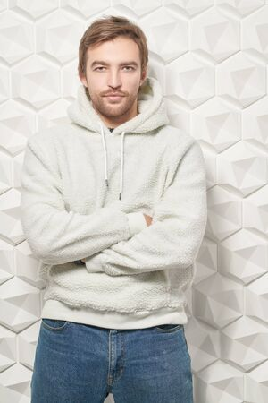Portrait of a handsome young man in white hoody and jeans. Men's beauty, fashion.