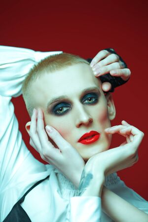 Portrait of a young man with women's makeup with numerous hands touching his face on a red background. Avant-garde fashion.