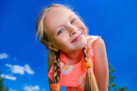 Happy little girl with pigtails in beautiful dress over blue sky. Children's fashion. Happy summer holidays.