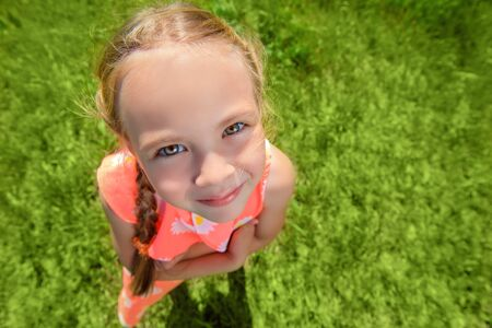 Happy little girl with pigtails in a summer park. Sunny day. Childhood. Kid's fashion. Stock Photo