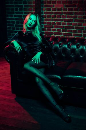 Portrait of a sexual blonde girl in evening dress sitting on a leather sofa in the night light. Beauty, fashion. Party style.