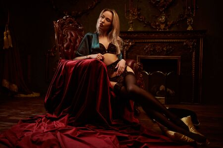 Attractive blonde girl in a black lace lingerie lies in a vintage armchair in a luxurious interior. Underwear fashion. Love concept.