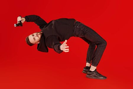 Handsome man in black clothes in motion in flight with a gun. Super agent on a mission. Criminal world, counterterrorism. Studio shot on a red background.