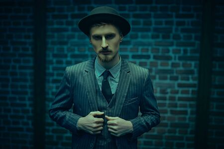 Portrait of a handsome young man in elegant suit and bowler hat standing in blue light by a brick wall. Men's fashion. Luxurious lifestyle.