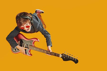 Happy emotional teen boy play the electric guitar listening to music in headphones on a yellow background. Copy space.