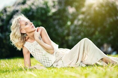 Ein Porträt einer älteren Frau, die sich auf dem Gras im Sommerpark entspannt. Schönheit, Gesundheitswesen.