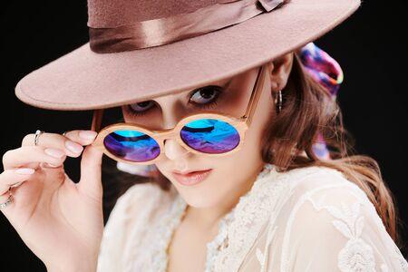Portrait of a modern girl wearing hat and sunglasses on a black background. Summer fashion. Boho, modern hippie style. Standard-Bild