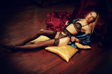 Jolie fille blonde dans une lingerie en dentelle noire se trouve dans un fauteuil vintage dans un intérieur luxueux. Mode de sous-vêtements. Notion d'amour.