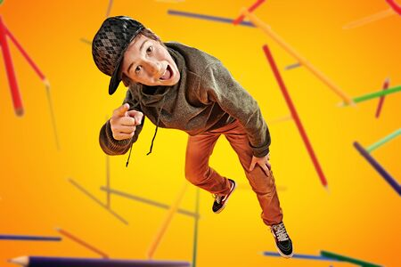Educational concept. Funny smart boy teenager student flies through the air like a superhero. Yellow background. Foto de archivo