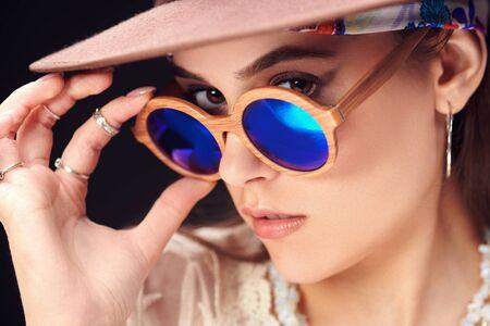 Porträt eines modernen Mädchens mit Hut und Sonnenbrille auf schwarzem Hintergrund. Sommermode. Boho, moderner Hippie-Stil.