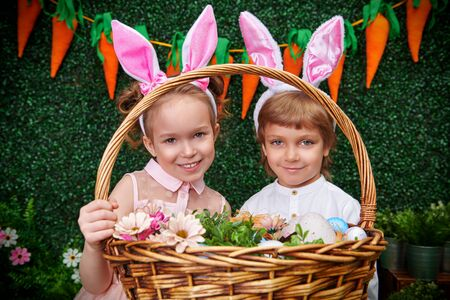 Cute smiling boy and girl with bunny ears are holding a basket with flowers and colorful eggs on the background of Easter decorations. Easter holiday.