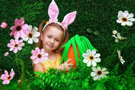 Cute smiling girl with bunny ears is holding a carrot and smiling surrounded by flowers and greenery. Beauty. Childhood. Spring-summer session.