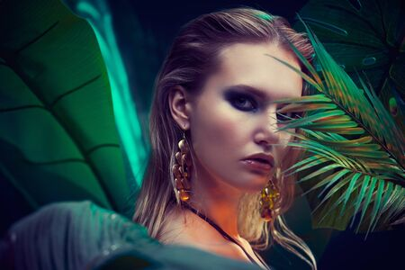 Portrait of a beautiful tropical woman with wet hair standing among palm leaves. Beauty, fashion and cosmetics concept. Vacation in tropical countries.