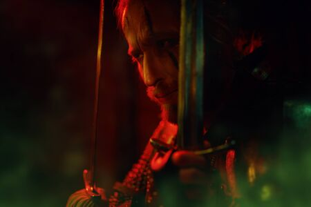 Portrait of a brave medieval warrior in armor with his sword in red light. The Witcher man. 免版税图像