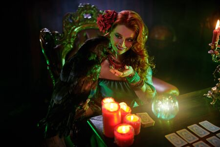 A beautiful red-haired fortune teller is talking to a black raven. The atmosphere of magic and sorcery, magic crystal ball and tarot cards.