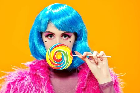 Attractive party girl with bright pink makeup and blue wig wears pink fur coat and holds big lollipop on a yellow background. Make-up and cosmetics, hairstyle. Fashion girl. Copy space.