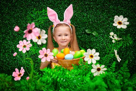 Cute smiling girl with bunny ears holds a nest with colored eggs on the background of Easter decorations. Easter holiday. Stock fotó