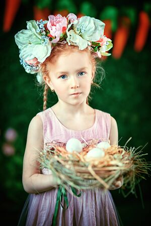 Portrait of redhead little girl in a flower wreath holding basket with white eggs. Beauty. Easter holiday. Childhood. Spring-summer season.
