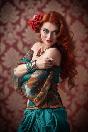 Portrait of a beautiful red-haired gypsy woman. National gypsy costume, ethnic. Make-up and hairstyle. Foto de archivo