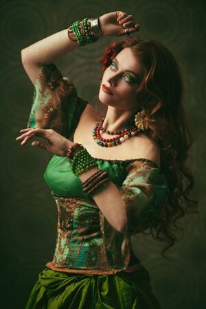 Beautiful red-haired gypsy woman is dancing. National gypsy costume, ethnic. Make-up and hairstyle.
