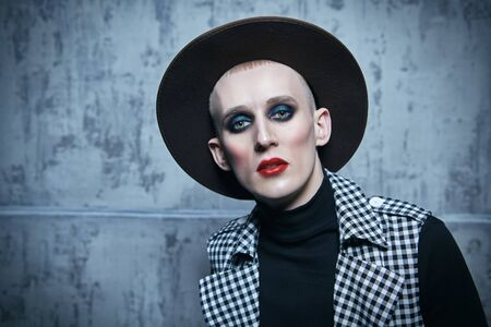 Portrait of a young man with women's makeup and clothing on a grunge background. Avant-garde fashion.