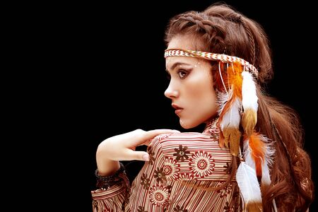 Portrait of a beautiful young woman with hairstyle and make-up in boho style. Bohemian, modern hippie fashion. Make-up, face painting and accessories.