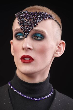 Portrait of a young man with women's makeup and with violet jewelry accessories on the head and neck on a black background. Avant-garde fashion.