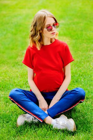 Young, pregnant woman in the summer park. Pregnancy and motherhood. Healthy lifestyle.