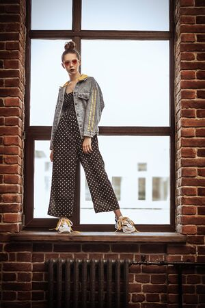 A full length portrait of a stylish bright fashionable girl posing on the windowsill indoor. Summer casual fashion.