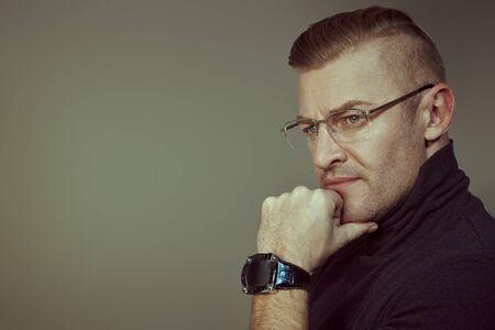 Handsome mature man in a black pullover and glasses thought deeply about something. Businessman portrait. Copy space. Wrist Watch style.