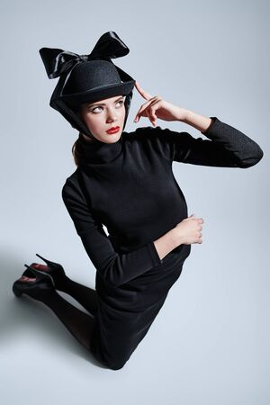 Fashion shot. Full length portrait of an elegant young woman in black fashionable hat and dress on a white background. Makeup and cosmetics. Copy space.