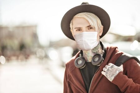 Coronavirus concept. Modern young man in a medical mask stands on the background of a big city. Stock Photo