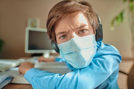 COVID-19 or coronavirus concept. A boy in a medical mask stares intently at the camera while being at home. Remote education. 免版税图像