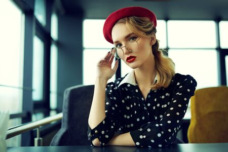 Portrait of an elegant young woman with make-up and clothes in pin-up style. Beauty, fashion. Optics and eyewear. Imagens
