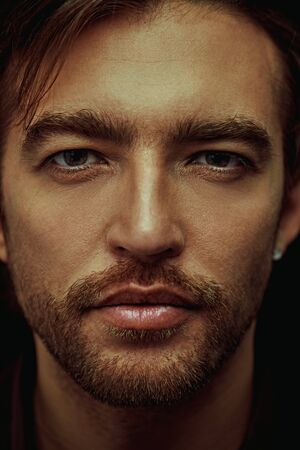 Close-up portrait of a masculine handsome man on a black background. Men's beauty. Business style, businessman. Studio shot. Foto de archivo