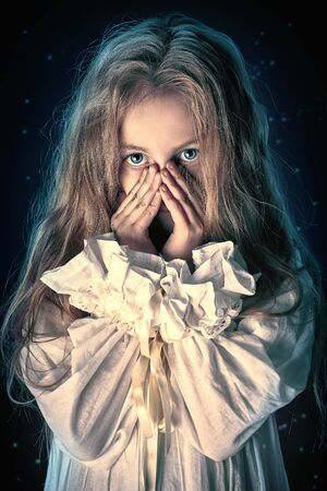 Portrait of a scary little girl ghost in a white nightgown. Black background. Halloween. Stock fotó