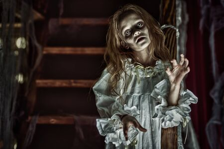 Little girl ghost in a nightgown wanders through the old house at night. Halloween.