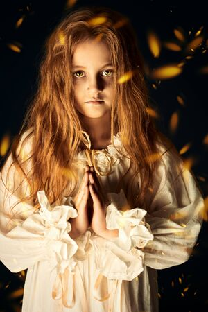 Scary little girl ghost in a white nightgown folded her hands in prayer. Black background. Halloween.