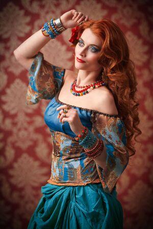 Belle femme gitane aux cheveux roux danse. Costume de gitan national, ethnique. Maquillage et coiffure.
