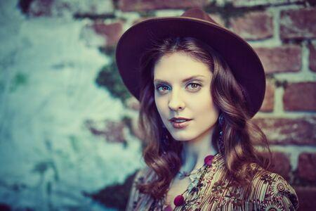 Porträt einer wunderschönen jungen Frau in Boho-Kleid und Accessoires, die vor dem Hintergrund der zerstörten Wände posiert, die mit Moos bewachsen sind. Böhmischer, moderner Hippie-Stil. Standard-Bild