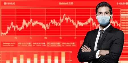 COVID-19. Portrait of a serious confident businessman in a medical mask against the background of stock charts. Copy space.