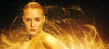 Beauty, fashion gold concept. Portrait of a beautiful girl model with golden skin and golden make-up on a sparkling background with golden lights. Jewelry. Cosmetics and beauty care. Standard-Bild