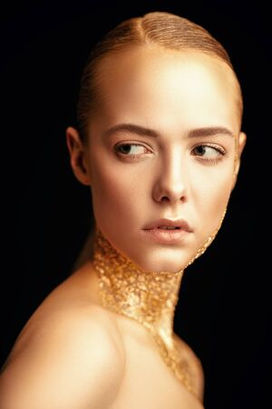 Beauty, fashion gold concept. Portrait of a beautiful girl model with golden skin and golden make-up on a black background. Jewelry. Cosmetics and beauty care.