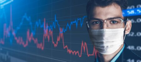 COVID-19 and business. Portrait of a serious confident businessman in a medical mask against the background of stock charts. Copy space. 免版税图像