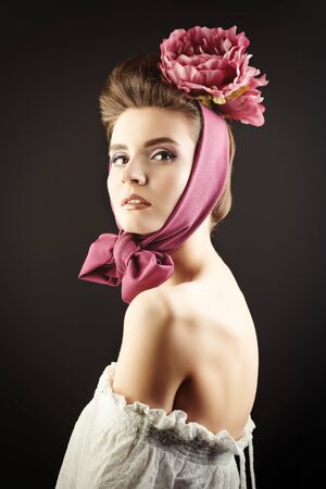 Elegant fashion model with a floral headdress. Fashion, clothing style, accessories. Studio portrait.
